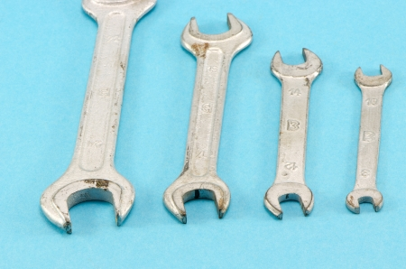 set different size hand wrench screw tools on blue background.  photo