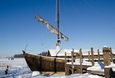 recreate: retro wooden ship frozen in lake ice near pier and sail on background of blue sky. people recreate in nature.  Stock Photo
