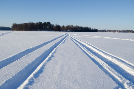 Snowmobile winter transport wheel marks left on frozen lake snow