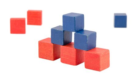 pyramid made of wood colorful toy log bricks blocks isolated on white  pink blue color construction   photo