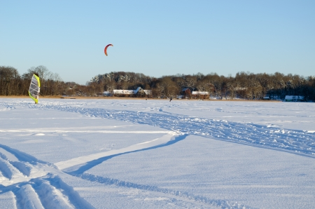 people kiteboarding and ice sailing on frozen lake in amazing cold winter day   modern recreation hobby   photo