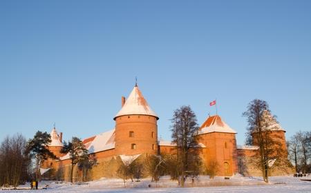 recreate: Beautiful sunset sunlight on Trakai castle in winter and people tourists recreate near it   Stock Photo