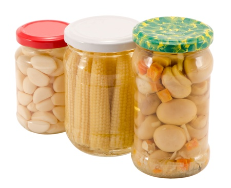 garlics corns champignon mushrooms canned preserved marinated in glass pots jars isolated on white  ecological organic food resource for winter   photo