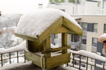 wooden small house birdie abundant snow covered roof on the balcony edge in cold winter time  photo