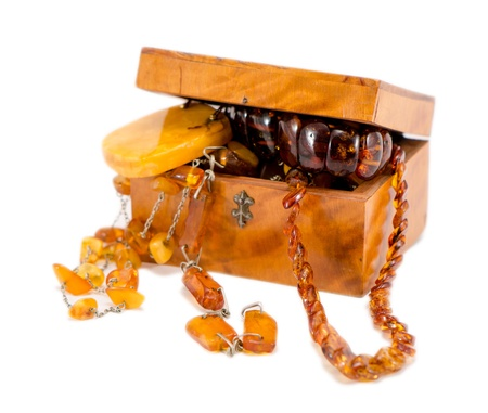 amber stone apparel jewelry in vintage wooden box chest isolated on white.