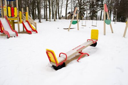 empty colorful playground surrounded by snow in winter. swing and other leisure equipment  for children.  photo