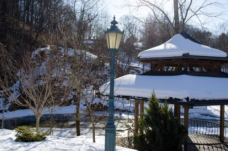 bower: wooden bower roof covered with snow and retro lighting lamp pole on river water bank waterside in winter park.