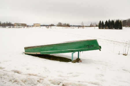 upturned: upturned wooden boat covered with snow rest on frozen lake shore bank waiting for warm season in winter.  Stock Photo