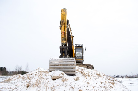 earthmover: earthmover excavator stand on quarry pile sand pit soil earth covered with snow in winter. heavy construction industry.
