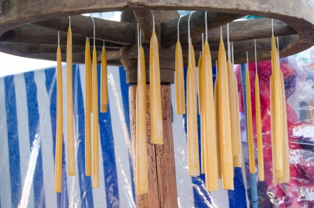 handmade hand dip yellow wax candles hang on retro wheel. traditional rural crafts.  Stock Photo