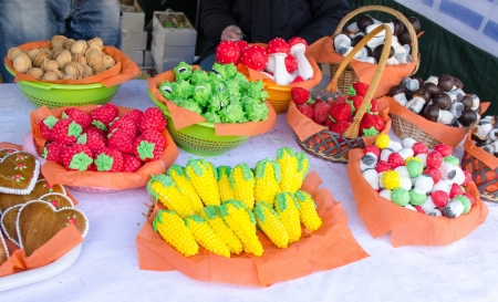sweet and savoury: various colorful mushroom corn strawberry chestnut shape sweets sold in market spring fair.  Stock Photo