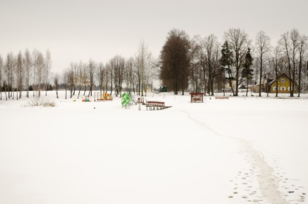 footpath through frozen lake and summer beach playground covered with snow in winter season.  photo