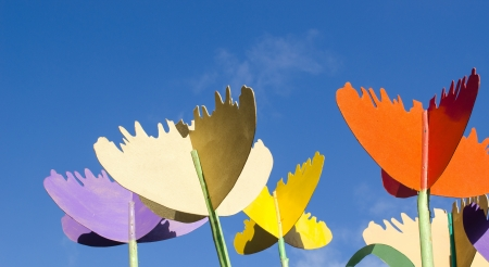 colorful stylized design decor tulips cut from plywood wood board against blue sky background.  photo