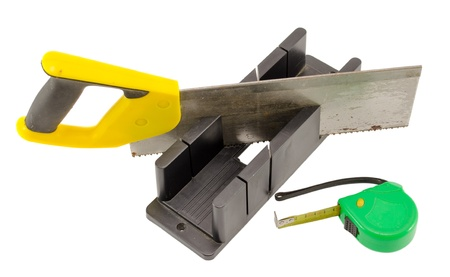 miter: plastic hand saw and angle cut miter box and measure tool isolated on white background.  Stock Photo