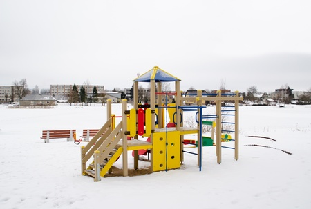 colorful playground on snowy frozen lake bank shore and living house district on other shore in winter.  photo