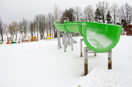 outdoor playground water park slide on frozen snowy lake in winter.  photo