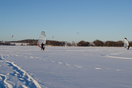 kiting: Lot of people ice sailing surfing and kiteboarding on frozen Galves lake in Trakai amazing cold winter day.  Stock Photo