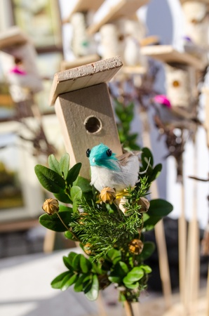sold small: small decoration wooden bird house box and little colorful handmade bird shape figure sold in outdoor spring easter fair market.