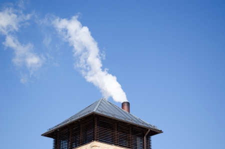 modern tin covered roof and white smoke rise from round chimney pipe on background of dark blue sky.  photo