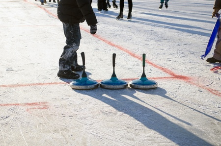 wintersport: people play winter game curling eisstock and slide skate playground on frozen lake ice.