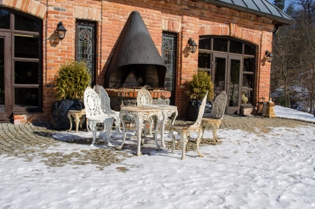 outdoor fireplace: retro decorative outdoor table and chairs near restaurant fireplace building between snow in winter.  Stock Photo