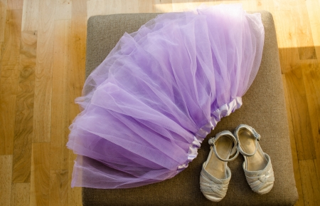 settee: girls blown lilac ballerina skirt and light gray shiny shoes lying on the settee  Stock Photo