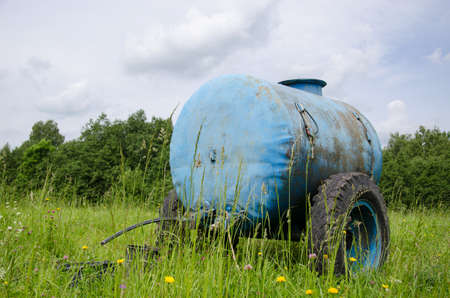 Blue water cistern for animal stand between pasture grass and clovers move in wind.  Stock Photo