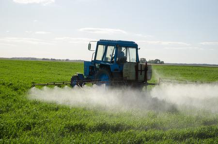 Traktor Spray düngen Feld mit Insektizid Herbizid Chemikalien in der Landwirtschaft Feld und Abend Sonnenlicht.