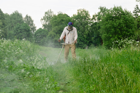 Worker man cut trim mow wet grass after rain. Water dew drops rise from meadow.