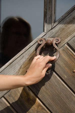 doorknocker: guest hand knock retro rusty metal door handle used as buzzer ringer knocker.