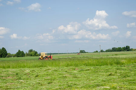 old color tractor cutting the grass a sunny summer day country landscape  photo