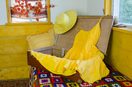 old open suitcase on bed with retro yellow summer dress and straw female hat