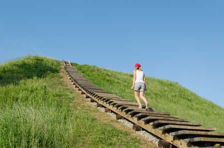 wooden stairs: tourist woman climb on mound hills in Lithuanian historic capital Kernave, UNESCO World Heritage Site.  Stock Photo