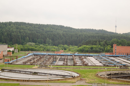 excremental: water treatment facility buildings. Sewage water cleaning reservoir. Birds fly.  Stock Photo