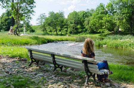 bewonderen: mooie vrouw zittend op wit bankje naast een snelstromende beek kijkt om zich heen te bewonderen natuur Stockfoto