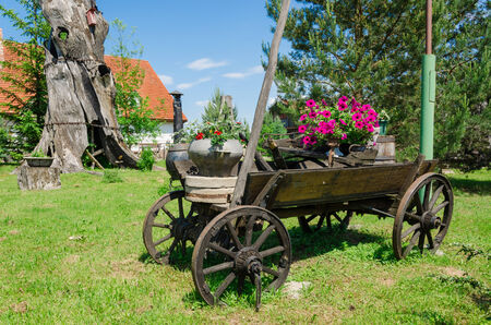 old rustic wooden rural carriage with summer flower composition village park