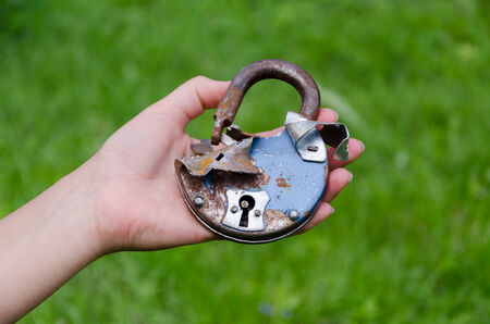 close up of old rusty broken door lock on man hand outdoor  photo