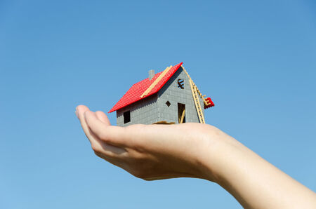house miniature model in female palm on blue sky background photo