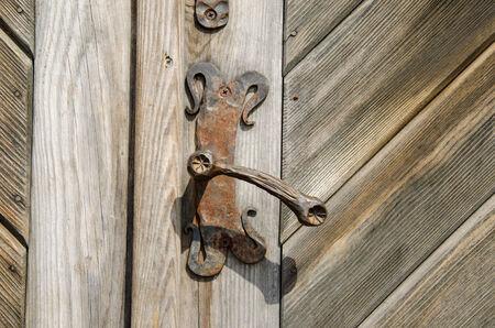 ancient rusty manor door handle on old wooden door  Stock Photo