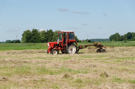 ted: tractor ted hay dry grass in agriculture field. Preparing feed for animals.
