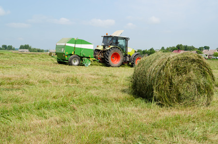 tractor bailer collect hay in field photo