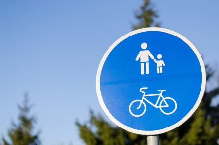 bicycle and pedestrian lane road sign on pole post in blue, walkway footpath route traffic roadside traffic sign  photo