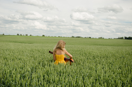 blonde girl with a yellow summer dress sitting in field of rye plays the guitar and swing  photo