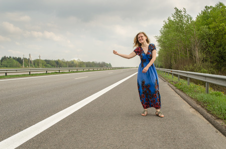 beautiful girl with long blue dress hitchhiking on the road