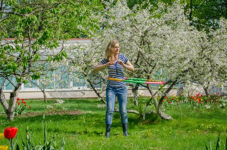 cintura perfecta: chica que da vuelta el aro entre cerezo floreciente tener una cintura perfecta