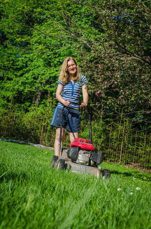 smiling country workwoman and fuel grass cutting machine in garden seasonal work  photo