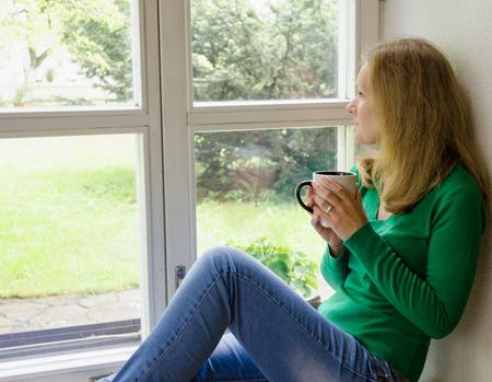 Sad worried broken hearted woman girl sit on wooden window sill and drink coffee tea.  Stock Photo