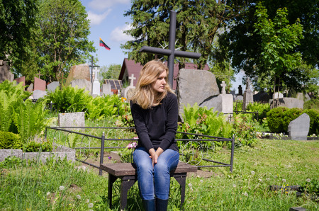 Sad woman sit near lover grave in cemetery. Patriot soldier died. National Lithuania flag.  Zdjęcie Seryjne