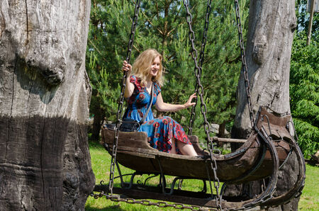 young blond woman swinging in ancient decorative swings antique wooden sleigh