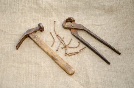 rusty hammer with nails and old pliers lying on linen texture  Stock Photo